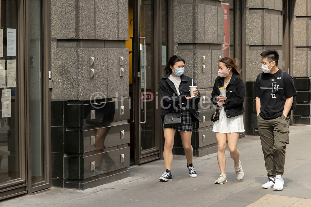 Young people wearing face masks walking along Bishopsgate in the City of London on 26th May 2021 in London, United Kingdom. As the coronavirus lockdown continues its process of easing restrictions, the City remains far quieter than usual, which asks the question if normal numbers of people and city workers will ever return to the Square Mile.