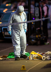 © Licensed to London News Pictures. 10/07/2015. London, UK. A forensics officer standing over a shoe and  bloodied clothing. Police and forensics forensics at the scene of a double shooting on Lordship Lame in Wood Green, north London in which a man has died and a woman is currently being treated in hospital.  Photo credit: Ben Cawthra/LNP