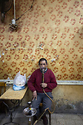 A man smokes a shisha pipe whilst watching television in an ahwah called 'Doctor' - allegedly nearly a century old. Islamic Cairo, Egypt