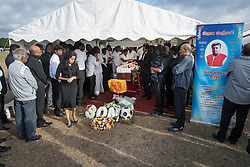 © Licensed to London News Pictures. 04/09/2016. London, UK. Relatives and friends pay respect in a tent holding the coffin of Nitharsan Ravi at a joint funeral held at Winn's Common Park for five men who drowned at Camber Sands last month.  The five men: Kurushanth Srithavarajah, brothers  Kenigan and Kobi Nathan, Inthushan Sri and Nitharsan Ravi were all friends from London.  They got into difficulty in the sea of Camber Sands on August 24. Photo credit: Peter Macdiarmid/LNP