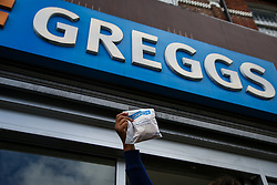 © Licensed to London News Pictures. 05/10/2021. London, UK. A woman holds a bag as she leaves a branch of Greggs in north London. Greggs, the bakery chain, warns of price increases of sausage rolls, pasties and steak bakes following the coronavirus and supply chain crises. Photo credit: Dinendra Haria/LNP