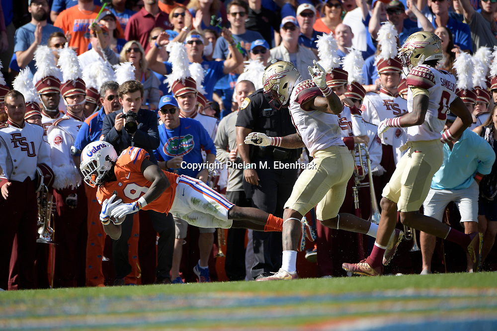 Florida wide receiver Dre Massey (9) dives for yardage after catching a pass in front of Florida State defensive back Derwin James (3), center, and defensive back Stanford Samuels III (8) during the first half of an NCAA college football game Saturday, Nov. 25, 2017, in Gainesville, Fla. (Photo by Phelan M. Ebenhack)