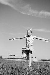 Young happy girl running field black and white