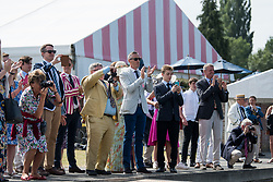 © Licensed to London News Pictures. 04/07/2018. Henley-on-Thames, UK. Family and friends of rowers watch as a team enters the water on day one of the Henley Royal Regatta, set on the River Thames by the town of Henley-on-Thames in England. Established in 1839, the five day international rowing event, raced over a course of 2,112 meters (1 mile 550 yards), is considered an important part of the English social season. Photo credit: Ben Cawthra/LNP