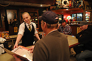 """Restaurant server Kellinah Wines helps a customer choose from the menu at """"R"""" Place Restaurant at the TA Travel Centers of America in Morris, Illinois."""