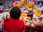 01 FEBRUARY 2017 - BANGKOK, THAILAND: A woman with her baby in her arms prays during Lunar New Year observances at the Poh Teck Tung Shrine in Bangkok. This is the Year of the Rooster in the Chinese zodiac and people pray and make merit to large statues of roosters in Chinese temples and shrines.     PHOTO BY JACK KURTZ