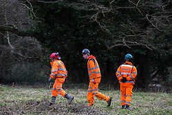 Denham, UK. 4 February, 2020. Engineers and a security guard walk across land cleared for works for the HS2 high-speed rail link project in front of an ancient alder tree with a girth of 11.6m and the river Colne. Planned works in the immediate vicinity are believed to include the felling of 200 trees and the construction of a roadway, Bailey bridge, compounds, fencing and a parking area. There is a wetland nature reserve adjacent to a Site of Metropolitan Importance for Nature Conservation (SMI) on the other side of the river.