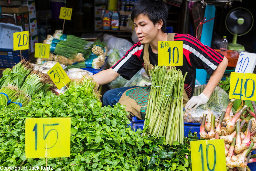 "24 AUGUST 2013 - BANGKOK, THAILAND: A produce vendor sits among the produce he was selling and their price signs in Khlong Toei Market in Bangkok. Thailand entered a ""technical"" recession this month after the economy shrank by 0.3% in the second quarter of the year. The 0.3% contraction in gross domestic product between April and June followed a previous fall of 1.7% during the first quarter of 2013. The contraction is being blamed on a drop in demand for exports, a drop in domestic demand and a loss of consumer confidence. At the same time, the value of the Thai Baht against the US Dollar has dropped significantly, from a high of about 28Baht to $1 in April to 32THB to 1USD in August.     PHOTO BY JACK KURTZ"