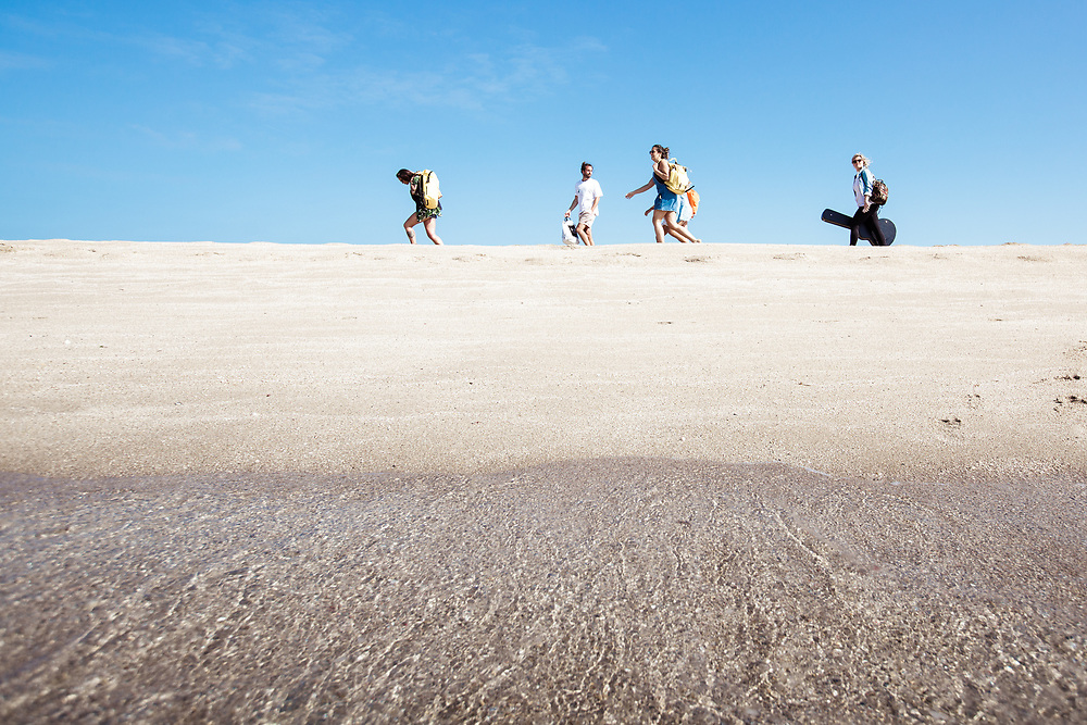 Crystal clear water lapping the shore, as friends walk along teh sandbanks taking in the views of the sea, sun and sand in Jersey, CI
