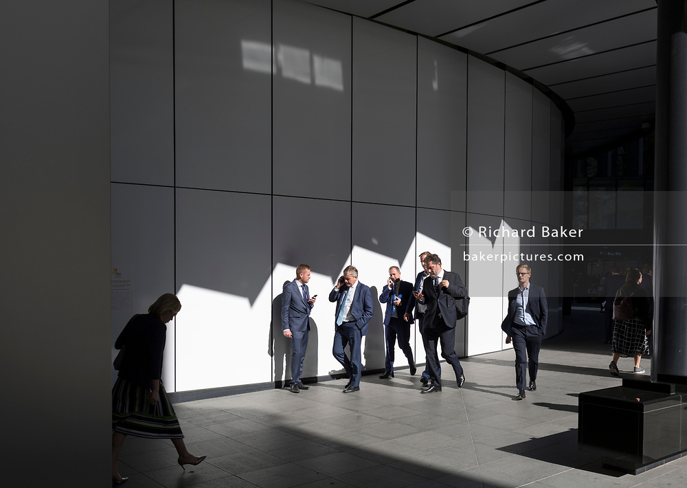 City workers enjoy warm sunshine outdoors on Fenchurch Avenue in the City of London - the capital's financial centre (aka The Square Mile), on 27th September 2018, in London, England.