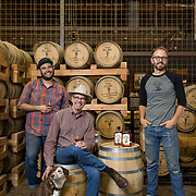 Tucson, AZ -- 09/28/2017<br /> <br /> (L- R) Hamilton Distillers' assistant distiller Ramón Olivas and his dog Scarlet, founder Stephen Paul and head distiller and maltser Nathan Thompson Avelino photographed in the barrel room at the Tucson distillery. <br /> <br /> Hamilton Distillers, makers of Whiskey Del Bac, is the first craft distillery in Southern Arizona since prohibition. The company produces three distinct single malt whiskeys, including Whiskey Del Bac Dorado which is malted over mesquite.<br /> <br /> The distillery offers tours and tastings on Saturdays at 3 p.m <br /> <br /> Photography by Jill Richards