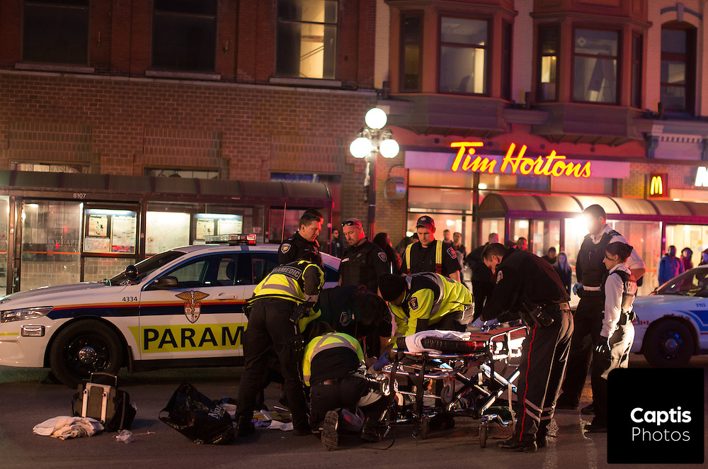 """Paramedics tend to a man who was assaulted on Rideau St. between Sussex Dr. and Dalhousie St. A witness said the victim made """"racist comments"""" being assaulted by multiple attackers.<br /> Police say the man was unconscious when being transported to hospital and is in non-life threatening condition. March 31, 2015.<br /> Captis Photos / Brendan Montgomery"""