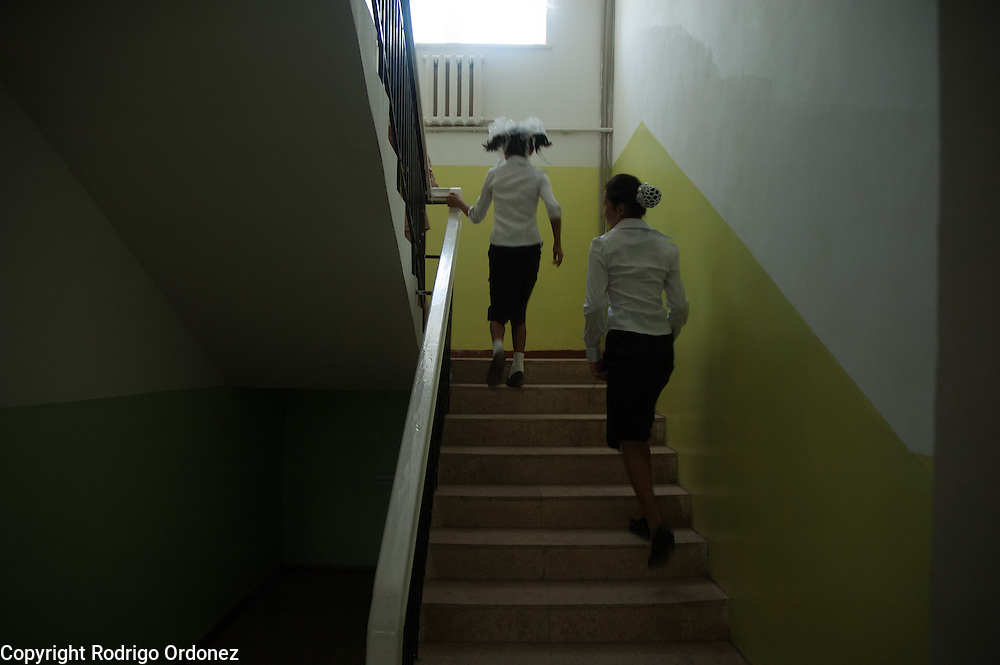 Girls in school uniform run upstairs in Mombekova School (in Osh, Kyrgyzstan) during the ceremony to mark the 'first bell', or first day of school, on September 1, 2010.