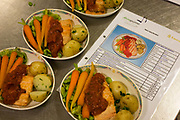 "Menu specification of a Business Class in-flight airline salmon meal are compared next to finished dishes in the world's largest independent provider of airline catering and provisioning services, Gate Gourmet, reaches out to add the last items in the company's factory on the southern perimeter road at Heathrow Airport, West London. Gate Gourmet serve more than 200 million meals on 2 million airline flights a year to their 250-plus airline customers at more than 100 airport locations around the globe. Apart from creating the bespoke meals for an airline's culture and ethnic demands, that pack the pre-flight carts, deliver and load into the aircraft galleys and afterwards, they dispose of the waste and strip, wash and sterilize the equipment. From writer Alain de Botton's book project ""A Week at the Airport: A Heathrow Diary"" (2009)."