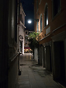 Narrow Venice street at night with a pedestrian at the intersection