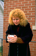 Woman age 27 holding morning coffee in the cool autumn.  WesternSprings  Illinois USA