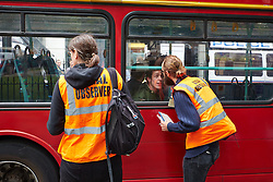 © Licensed to London News Pictures.  11/06/2013. LONDON, UK. Two legal observers talk to an arrested anti G8 protester waiting in a red London bus.  Photo credit: Cliff Hide/LNP