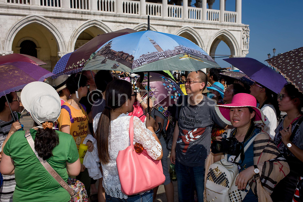 Chinese tourists with umbrellas at the Doge's Palace in Piazza San Marco, Venice, Italy. The wide expanse of Piazza San Marco is in the heart of Venice and where, for most daylight hours, the pavement is crowded with humanity as the influx of tourists who, in their own way, flood the narrow streets with sun-shading umbrellas and the smaller canals with gondolas. Venice attracts 22-million visitors each year (for a city of only about 60,000 residents) while the cultural protection organisation, Italian Nostra, warns that Venice can only accommodate about 33,000 visitors per day but currently at least 60,000 daily.