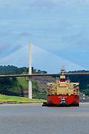 Ship crossing through Culebra Cut under the Centenial Bridge at the Panama Canal.<br /> Buque cruzando el Corte Culebra por el Puente Centenario en el Canal de Panama.