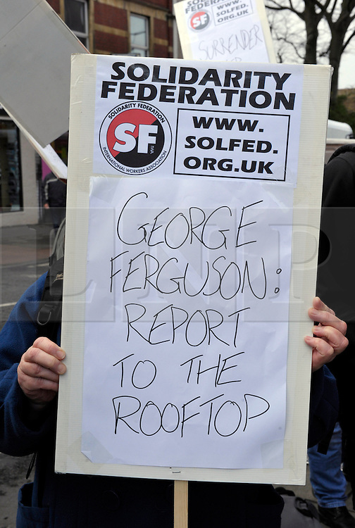 """© Licensed to London News Pictures. 14/12/2013; Bristol, UK.  Anti cuts protesters, including one with a placard saying """"George Ferguson: report to the roof top"""", demonstrate against proposed cuts to Bristol City Council's budget outside the Tobacco Factory cafe bar, which is owned by the Mayor of Bristol, George Ferguson who also has accommodation on the top floor of the building.  As Mayor of Bristol, George Ferguson has proposed cuts of 25% of the council budget and the equivalent of 800 full time job losses from the council's staff.  14 December 2013.<br /> Photo credit : Simon Chapman/LNP"""