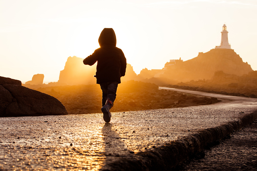 Boy running towards the sunlight at the walkway of the tourist attraction Corbiere lighthouse, in Jersey, Channel Islands