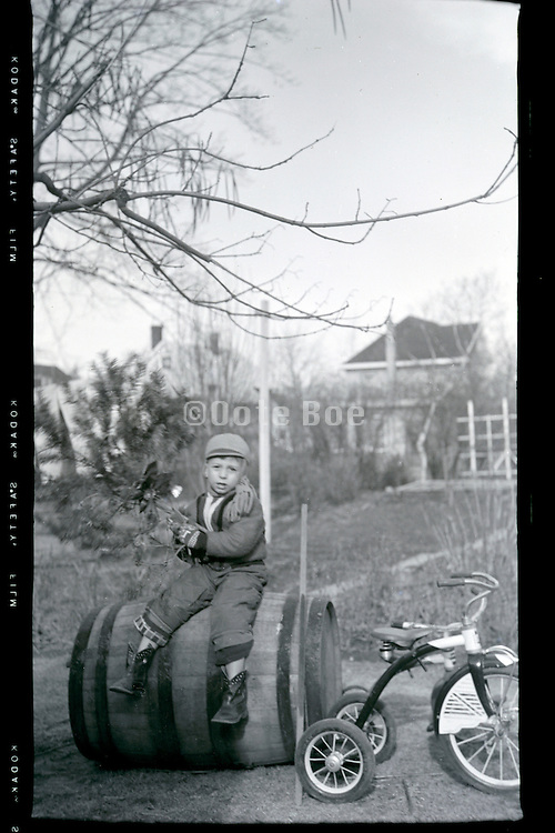 young boy with tricycle in backyard 1950s