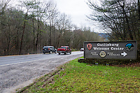 Sign on the entrance to the Gatlinburg welcome center in the Great Smoky Mountains National Park with cars behind