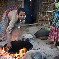 """Wubalem prepares a breakfast of injera (a yeast-risen flat bread) with her daugher Rekebki in the kitchen area at the back of their home.<br /> <br /> Wubalem Shiferaw, age 23, lives in the village of Mecha with her husband Tsega Bekele, age 33, and their daughter Rekebki, age 4. Wubalem remembers her grandparents harvesting honey. She has maintained this tradition while moving to modern hives which produce a far greater yield of honey. Wubalem is a member of the Mecha village Cooperative which brings together local women beekeepers allowing them to share insights and build a credit union. The Mecha village Cooperative is not yet a member of the Zembaba Union. Wubalem's husband Tsega is a priest and a tailor. <br /> <br /> Harvesting honey supplements the income of small farmers in the Ethiopian region of Amhara where there is a long tradition of honey production. However, without the resources to properly invest in production and the continued use of of traditional, low-yielding hives, farmers have not been able to reap proper reward for their labour. <br /> <br /> The formation of the Zembaba Bee Products Development and Marketing Cooperative Union is an attempt to realize the potential of honey production in Amhara and ensure that the benefits reach small producers. <br /> <br /> By providing modern, high-yield hives, protective equipment and training to beekeepers, the Cooperative Union helps increase production and secure a steady supply of honey for which there is growing demand both in and beyond Ethiopia. The collective processing, marketing and distribution of Zembaba's """"Amar"""" honey means that profits stay within the cooperative network of 3,500 beekeepers rather than being passed onto brokers and agents. The Union has signed an agreement with the multinational Ambrosia group to supply honey to the export market. <br /> <br /> Zembaba Bee Products Development and Marketing Cooperative Union also provides credit to individual members and trains carpenters in"""