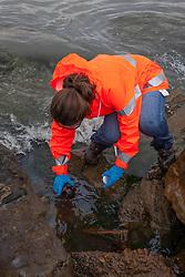 Relief worker taking water samples.
