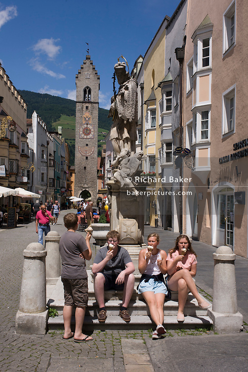 With the Zwölferturm clocktower in the distance, tourists sit beneath the St. John of Nepomuk monument in front of the Town Hall in Sterzing-Vipiteno, South Tyrol, northern Italy. The Zwölferturm is a 46m high tower erected in 1470, it is the symbol of the city that divides the New Town from Old Town Sterzing.