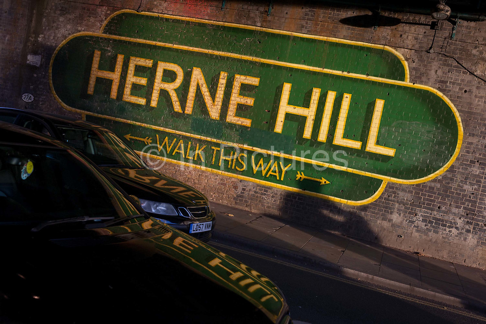 Reflected in a car bonnet is the large sign under the railway bridge announcing Herne Hill, Lambeth SE24 on 18th November 2016, in south London, England.