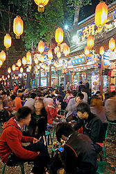 Many people waiting outside popular restaurant at night on Ghost Street in Dongzhimen district of China