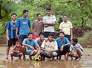 Portrait of local youths that play football during the monsoon season. Mangalore, Karnataka, India.