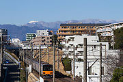 Mount Fuji seen over suburban Kanagawa, with a  Tobu 50050 series, commuter train passing through Tsukumino, Japan, Thursday February 27th 2020