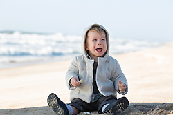 baby smiling while playing on the beach in the Winter