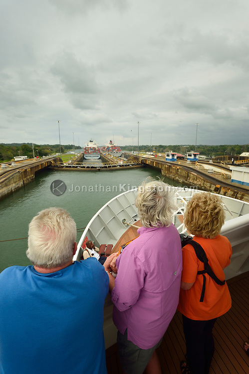 Passengers of a small cruise ship watch from the deck as the ship transits the Gatun locks, on the Atlantic side of the Panama Canal, Panama.