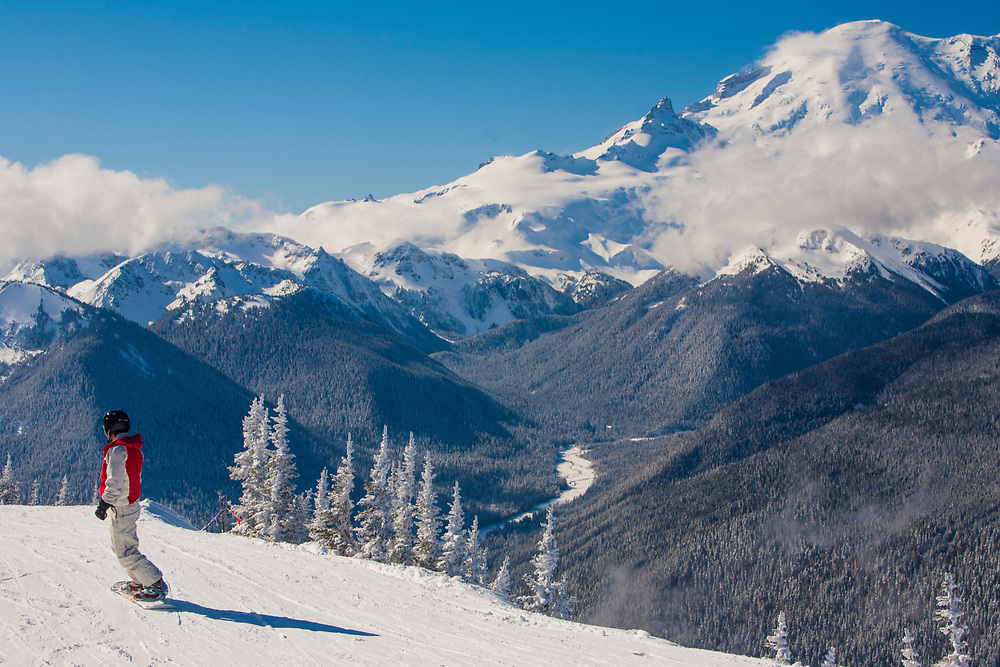North America, United States, Washington, person on snowboard at Crystal Mountain, with Mt. Ranier in distance