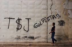"""A woman walks beneath an overpass by graffiti that reads """"The coup plotting Supreme Court"""".  Today marks the end of the initial 10 day period the court had to designate members of the National Electoral Council.  The NEC is the body that will ultimately be able to authorize and validate signatures calling for a presidential recall."""