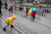 A young boy picks up a dropped toy car and a middle-eastern family whose colours of the spectrum are on their brolley while visiting Trafalgar Square, Westminster, on 9th April 2019, in London, England.