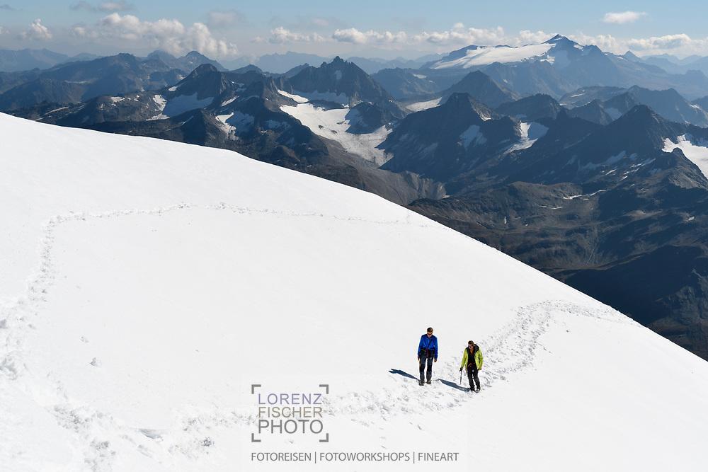 Zwei Alpinisten steigen über die Firnflanke zum Gipfel des Galenstocks auf. Im Hintergrund die Lepontischen Alpen mit Pizzo Rotondo und Basodino, Furka, Uri, Schweiz<br /> <br /> Two alpinists are climbing the firn field on to the top of Galenstock. The Lepontine Alps with Pizzo Rotondo and Basodino in the background, Furka, Uri, Switzerland