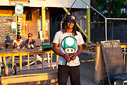 Local resident restaurant owner, dreadlocks and cap, smiling at camera, afternoon light. Caye Caulker island ocean view and jetee at dusk, Belize.