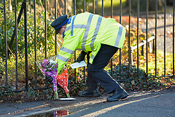 © Licensed to London News Pictures. 19th December 2014. Essex, UK. A police officer placing flowers at the scene of the murder of an 18 year old male who was fatally stabbed yesterday at the Chelmsford Museum, Oaklands Park, Moulsham Street, Chelmsford. Two males aged 17 and 19 have been arrested in relation to this matter and remain in custody. Photo credit : Simon Ford/LNP