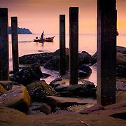Small boat cruises past pier posts at dusk (Koh Kood (Ko Kut) island, Thailand - Oct. 2008) (Image ID: 081016-1838041a)