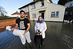 © Licensed to London News Pictures. Date 9 Jan 2014. Oxford. Neil Braich and his mum and nephew try to stop the flood waters with sand bags on the Abingdon Road.<br /> River Thames floods at Oxford causing the closure of the Abingdon and Botley roads.. Photo credit : MarkHemsworth/LNP