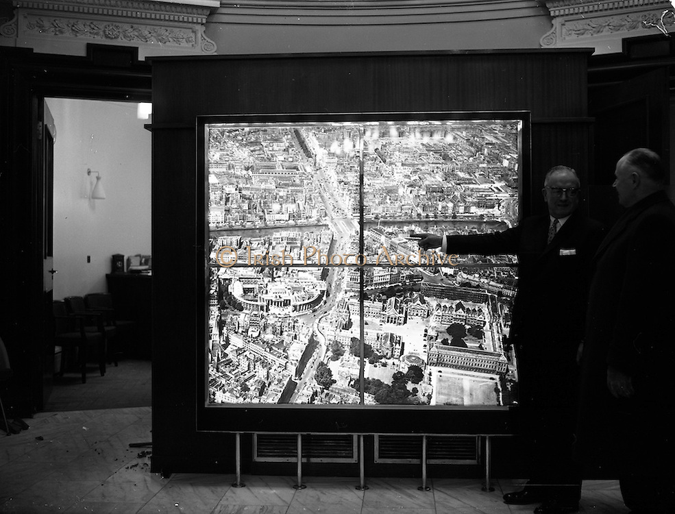 24/01/1962<br /> 01/24/1962<br /> 24 January 1962<br /> Illuminated map at Ulster Bank, College Green, Dublin. A large hand coloured illuminated photograph depicting the principal feature of central Dublin was put on display in Ulster Bank. It was an aerial view of the city centre enlarged to five feet by five feet nine inches from a transparency of 5 by 4 inches. The bank felt that it would be of interest to customers and tourists alike. Picture shows the manager of the bank, Mr S. le F. Killingley pointing out a landmark to a customer. Photos, Photo, Snap, Streets, Street,