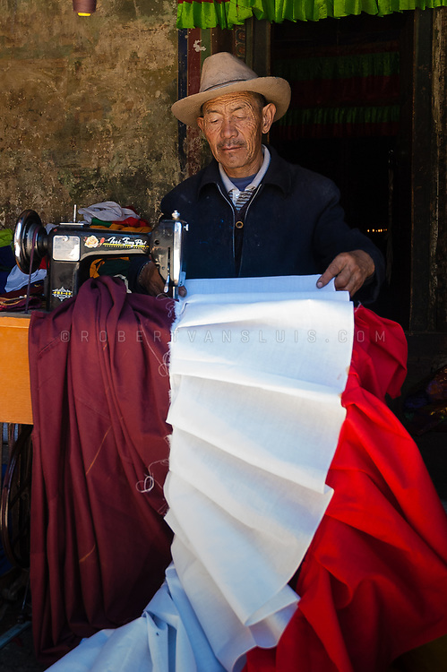 Man operating a sewing machine at Samye Monastery, Tibet, China. Photo © robertvansluis.com