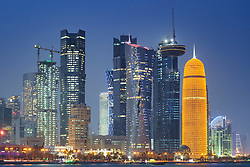 Night view of skyline along waterfront of Corniche towards modern office towers in West Bay Doha Qatar