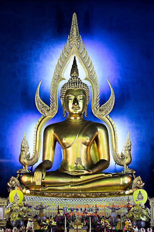 Golden Buddha Blue: In the Marble Temple, a golden Buddha statue sits in a lotus position atop an intricately decorated alter, Wat Benjamabophit, Bangkok Thailand.