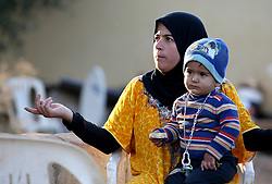 A Syrian refugee and her child in a settlement camp where they live amongst an olive grove in Koura, near Tripoli, Lebanon.
