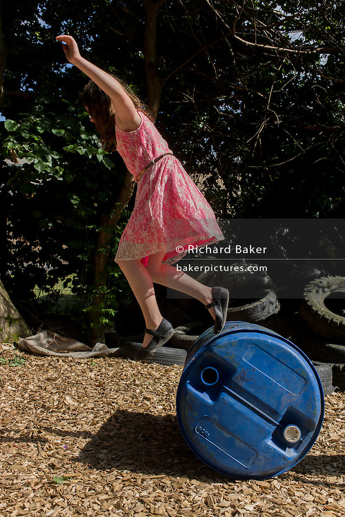 Children play with barrel in risk averse playground called The Land on Plas Madoc Estate, Ruabon, Wrexham, Wales.
